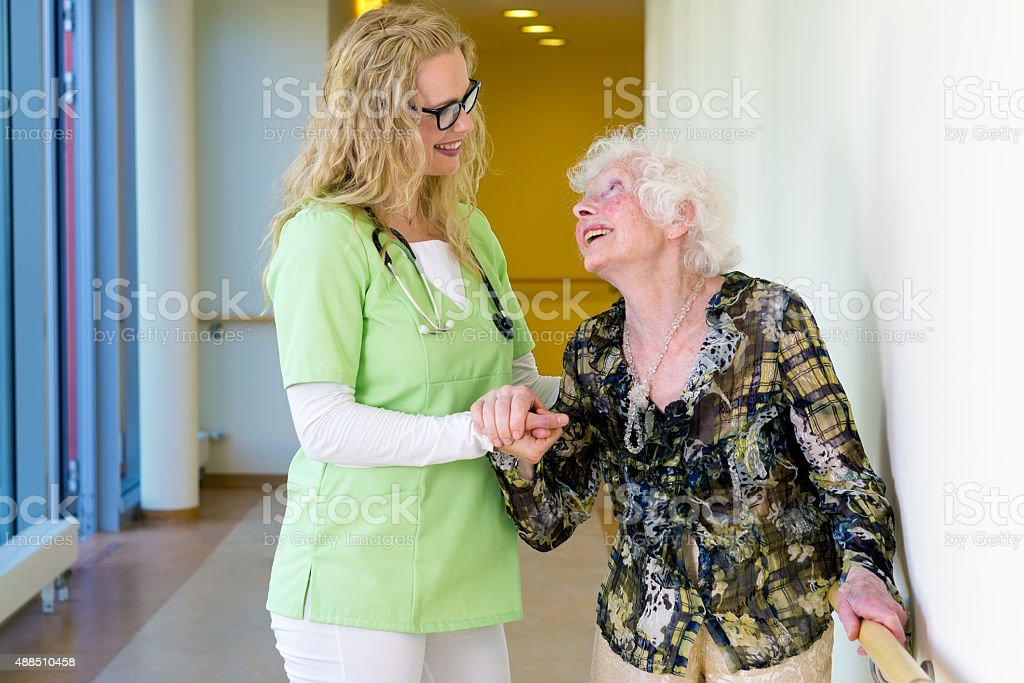 Therapist Assisting Elderly Walking In Hospital. stock photo