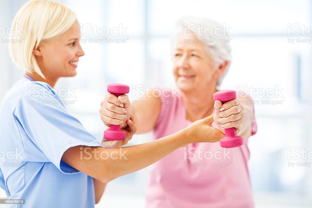 Therapist Assisting Senior Woman In Lifting Dumbbells stock photo