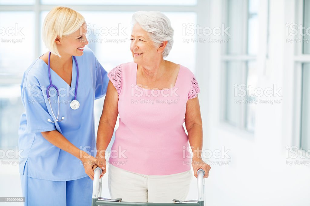 Therapist Assisting Senior Woman With Walker stock photo