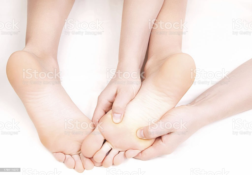 Therapist doing a foot massage,  pressing reflexology zones stock photo