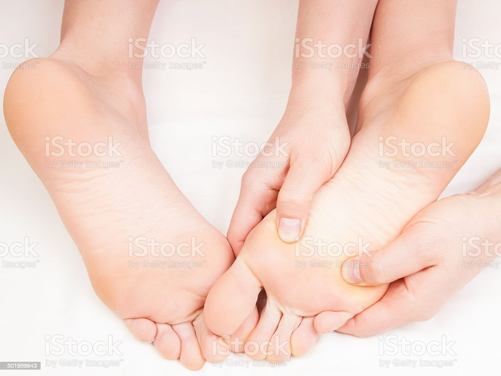 therapist doing a foot massage pressing reflexology zones stock photo