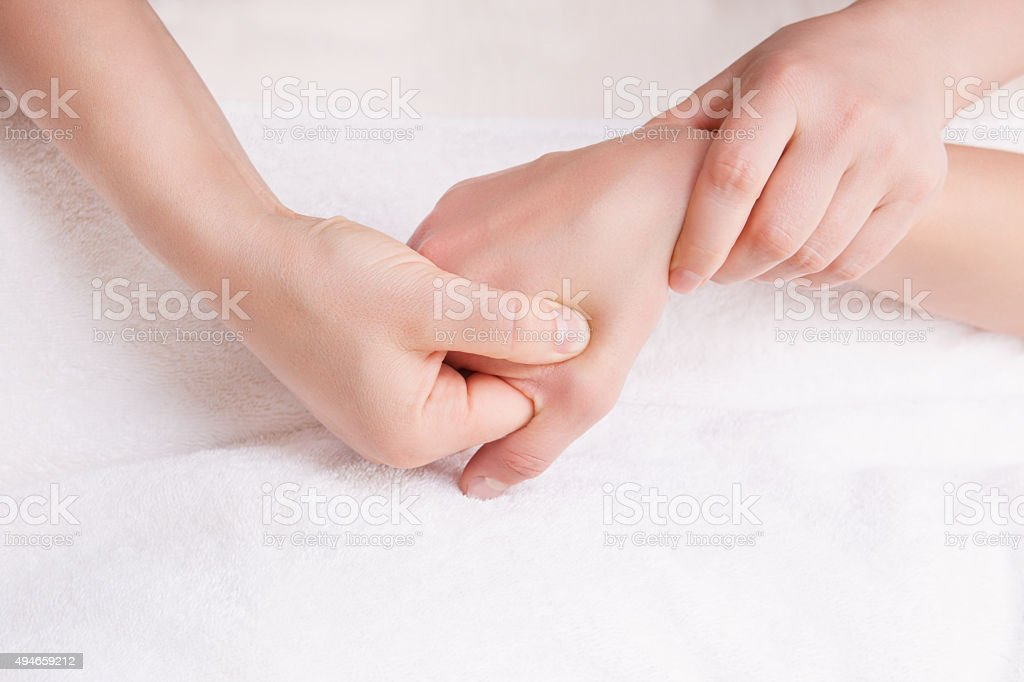 Therapist doing a pressure point massage on the womans hand stock photo