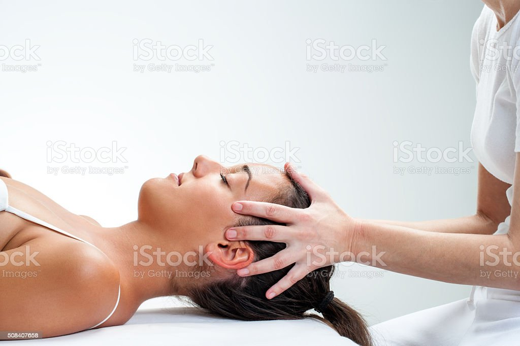 Therapist doing healing osteopathic treatment on woman. stock photo