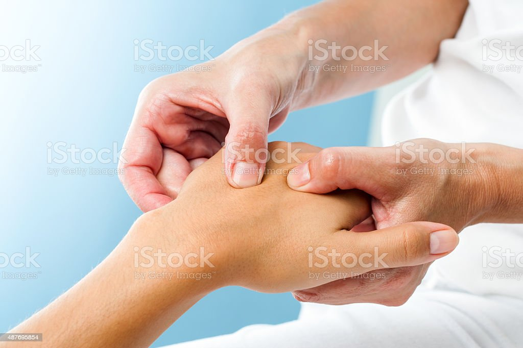Therapist doing massage on female hand. stock photo