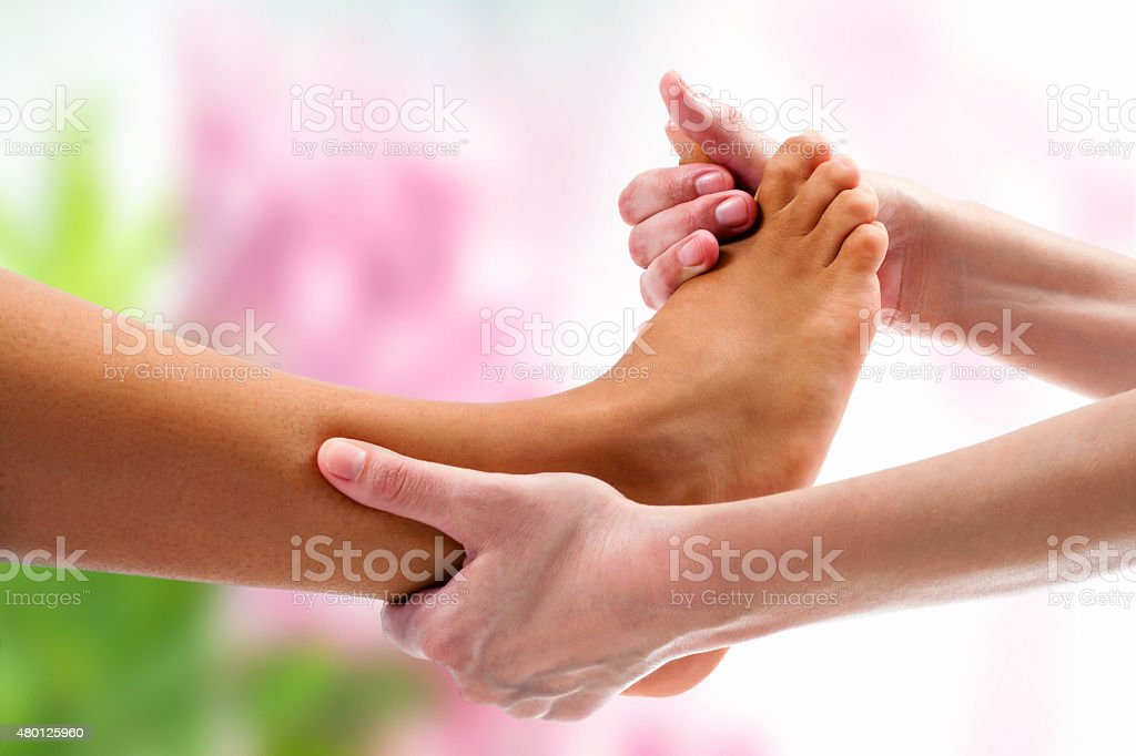 Therapist doing osteopathic massage on foot. stock photo