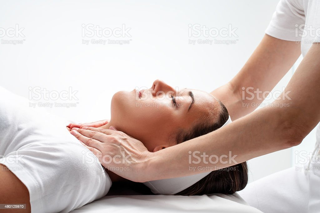 Therapist doing reiki on woman?€™s neck. stock photo