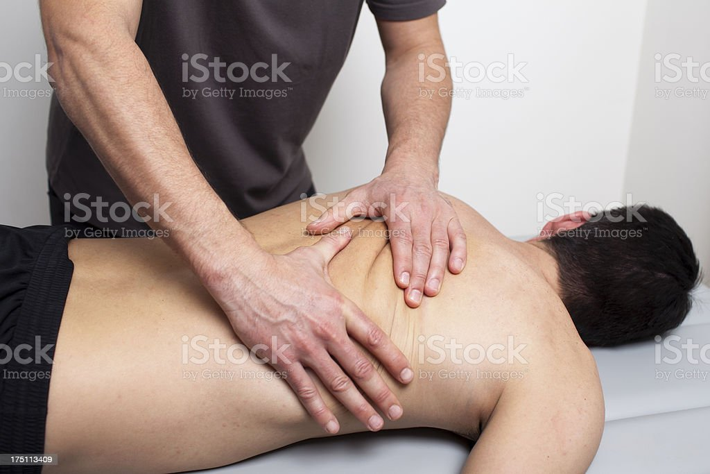 therapist giving a back massage stock photo