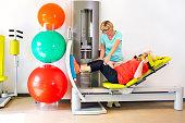 Therapist helps woman strengthen leg muscles.