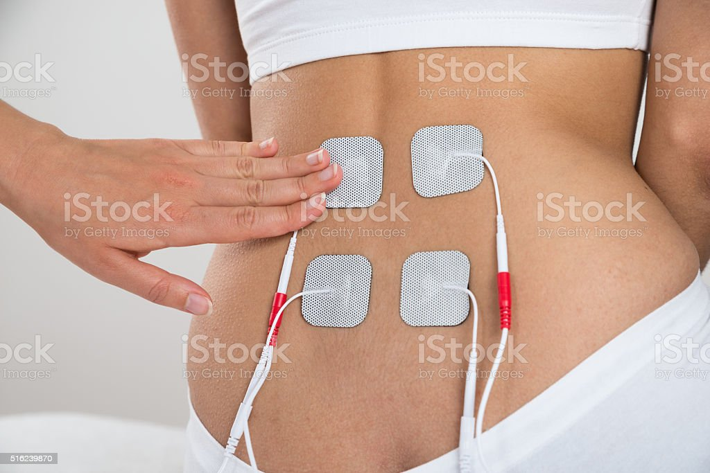 Therapist Placing Electrodes On Woman's Back stock photo