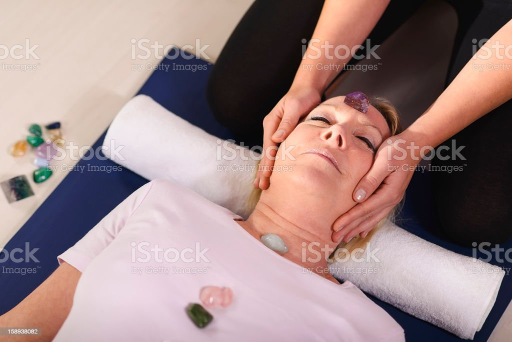 Therapist using crystals on client for Reiki stock photo