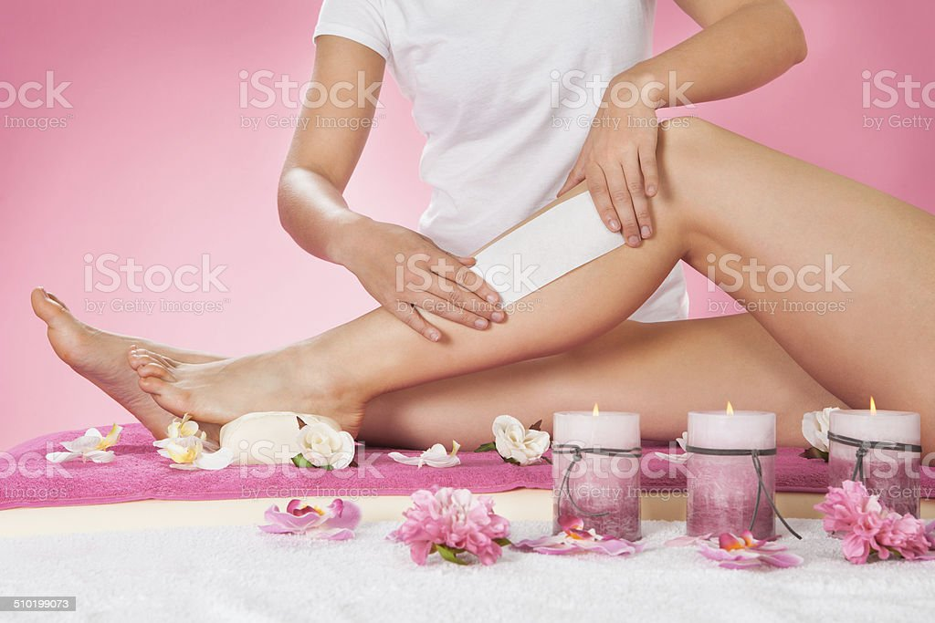 Therapist Waxing Customer's Leg At Spa stock photo