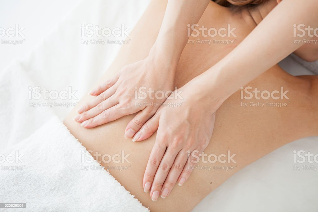 Therapist who massages a woman's back for health stock photo