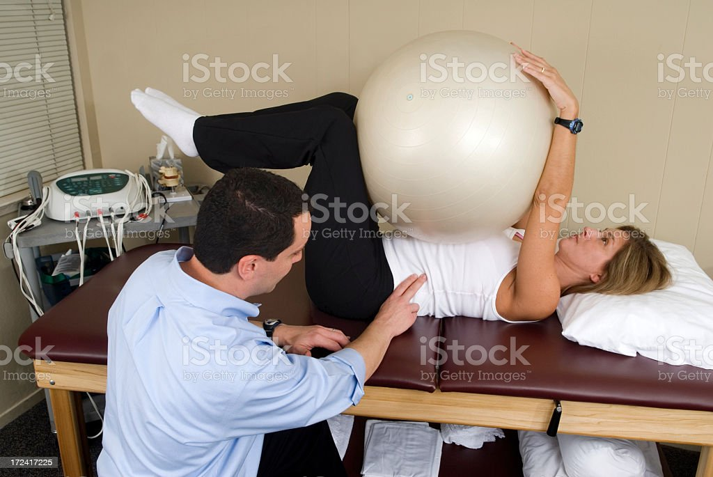 Therapist working with woman patient and fitness ball royalty-free stock photo