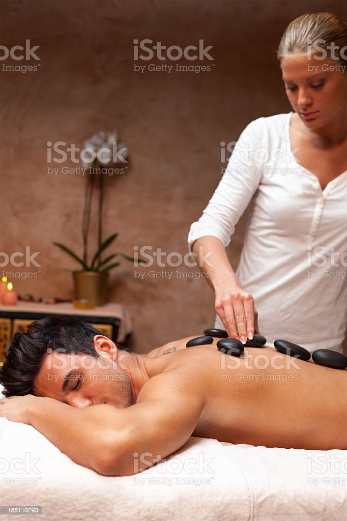 Therapists giving lastone massage to a man royalty-free stock photo