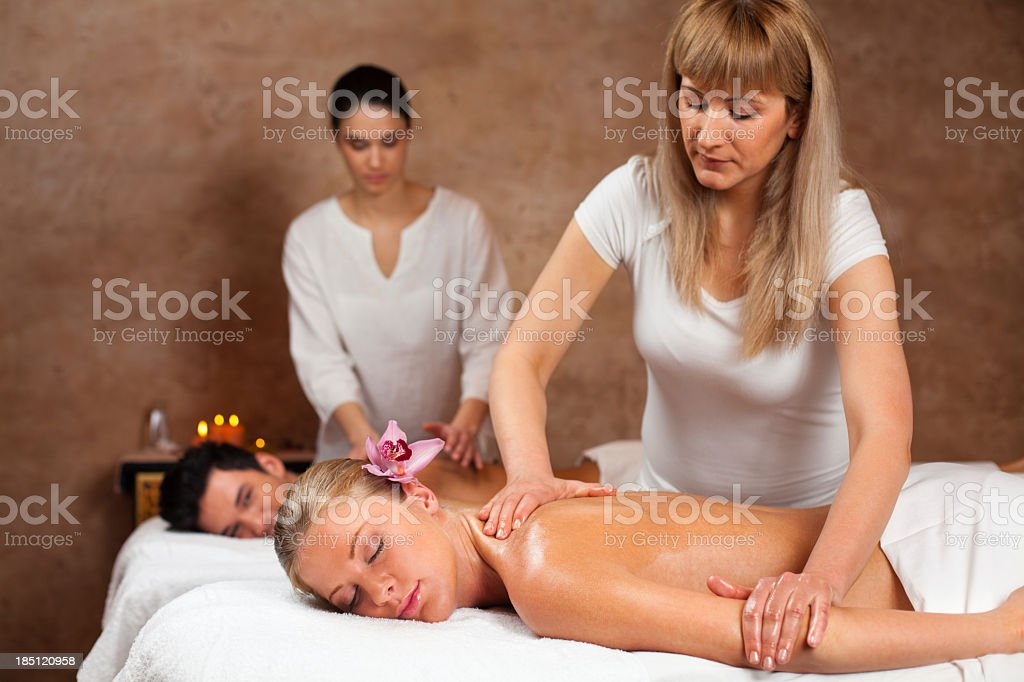 Therapists giving massage to a couple at health spa royalty-free stock photo