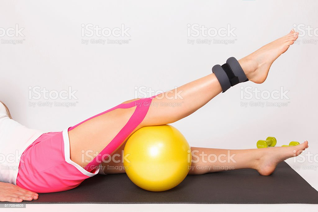 Therapy for leg injury with ball and kinesio tape stock photo
