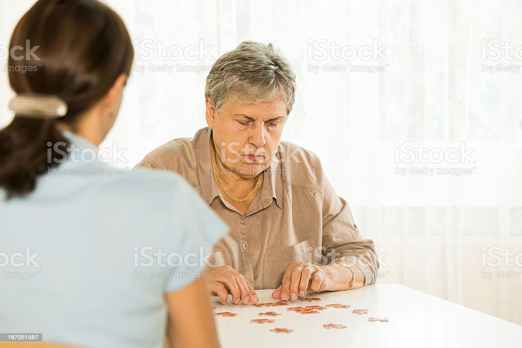 Therapy: Senior woman with puzzle royalty-free stock photo