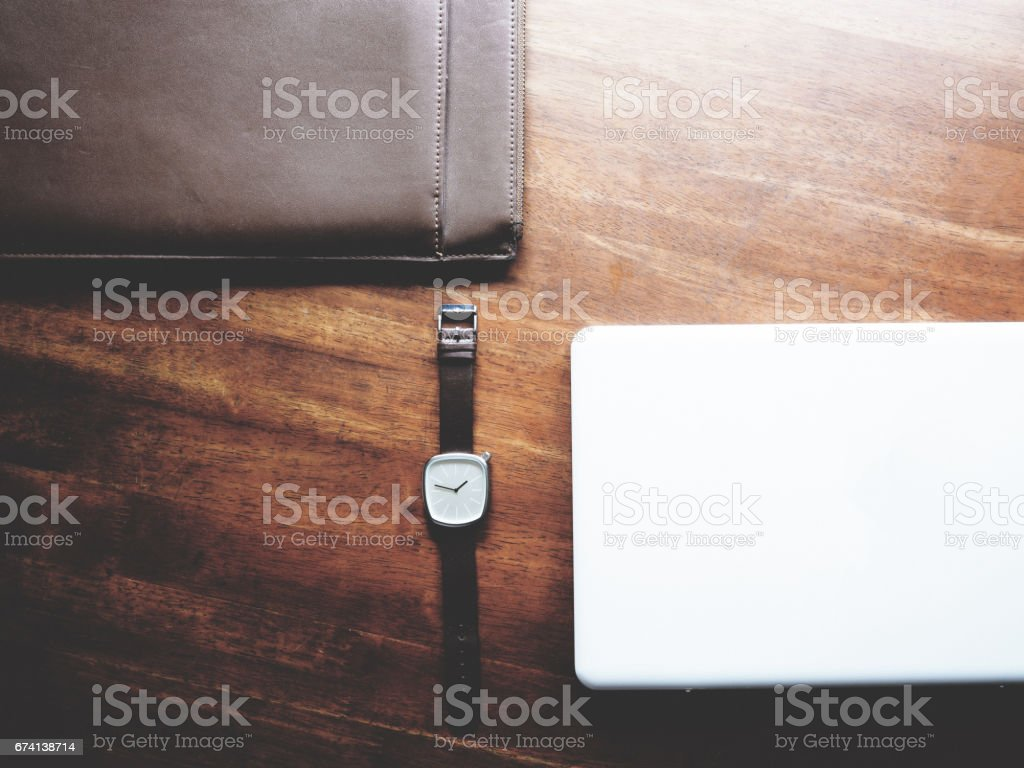 there are watch, leather bag and laptop on wooden table, minimal style, soft tone stock photo