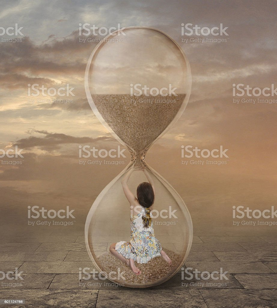 There is a girl into a hourglass. stock photo