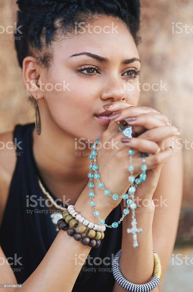 Shot of an attractive young woman praying with her rosary...