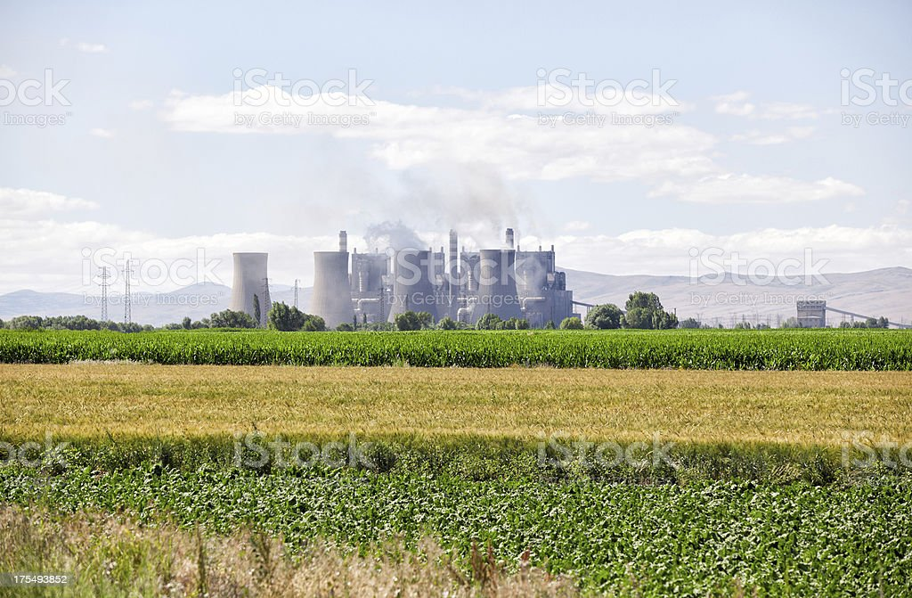 A thermal power plant at background of big agricultural area stock photo