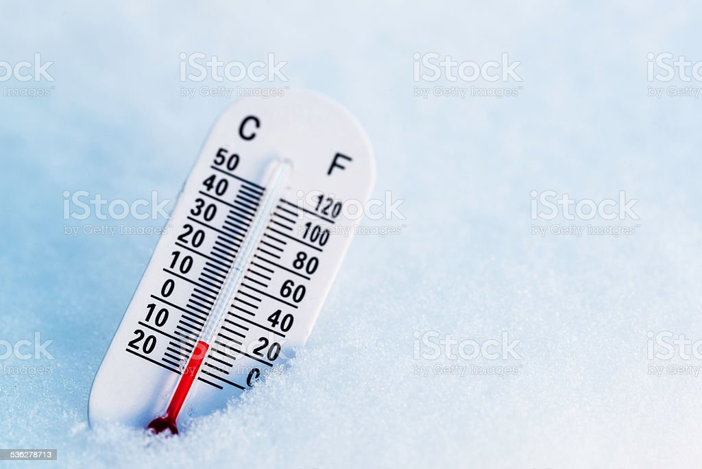 Thermometer in the snow with both celcius and fahrenheit stock photo