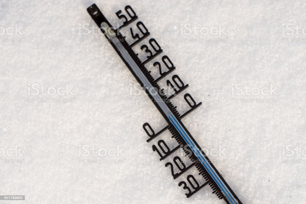 Thermometer on snow shows low temperatures in degrees Celsius stock photo