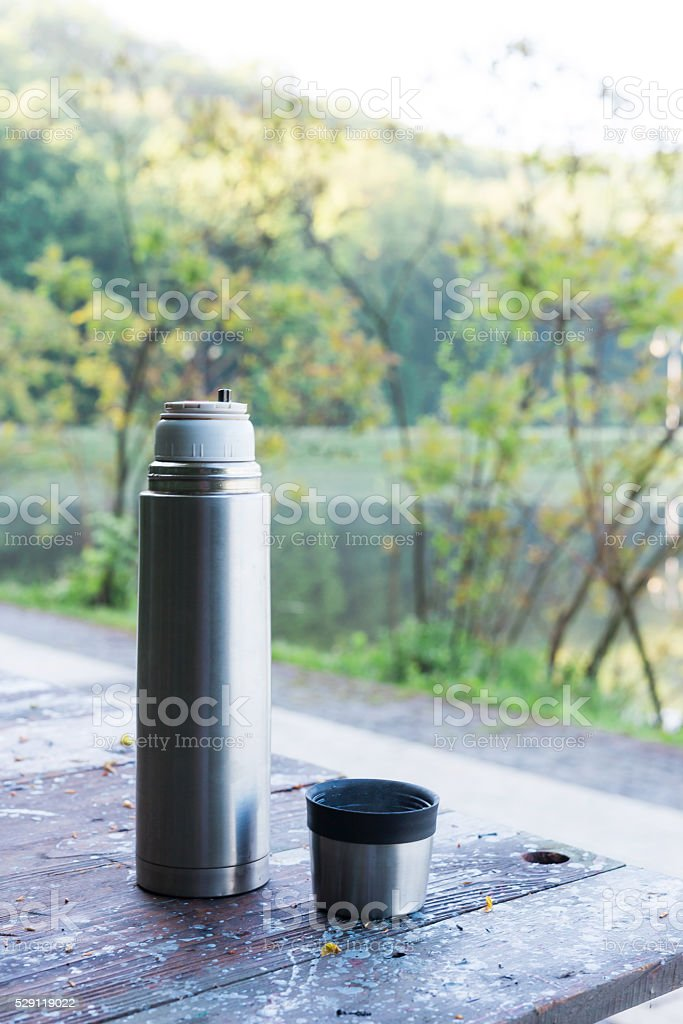 Thermos  and cup of coffee on wooden table stock photo