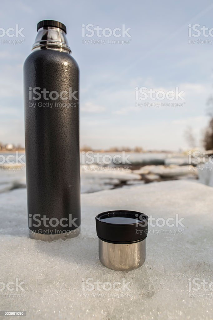 Thermos and cup with hot drink standing on the ice stock photo