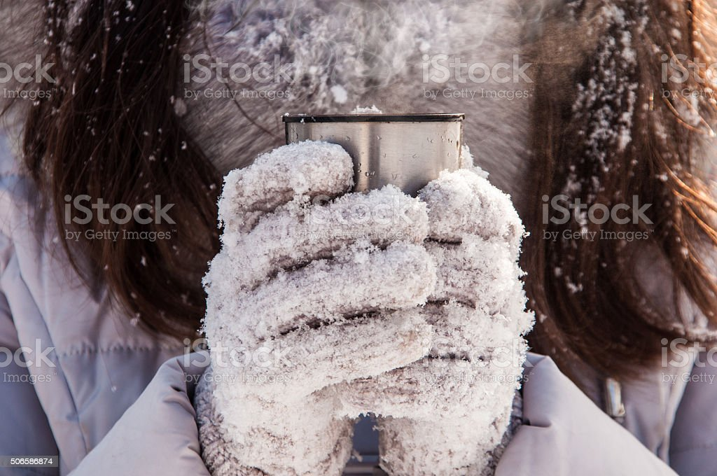 thermos cup in hands of the girl in the winter stock photo