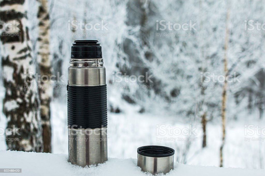thermos in snow stock photo