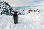 Thermos on the snow in the mountains.