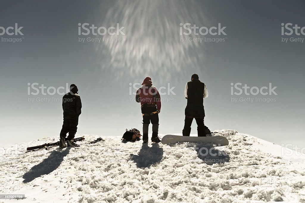 They gaze in awe. Three men on mountain top. stock photo