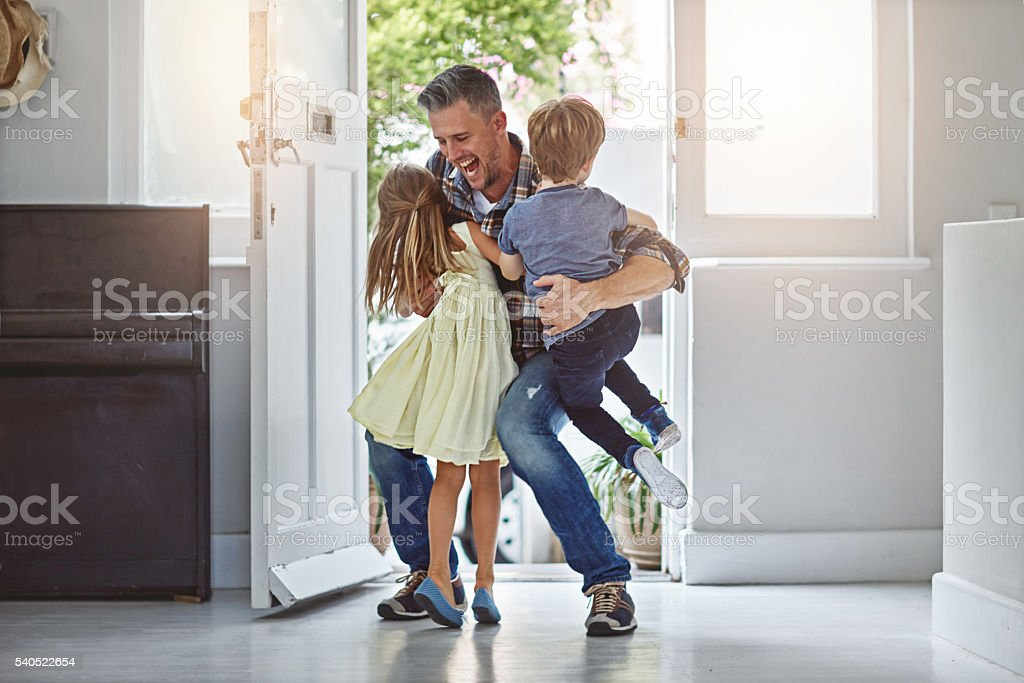 They hang all over him when he gets home stock photo