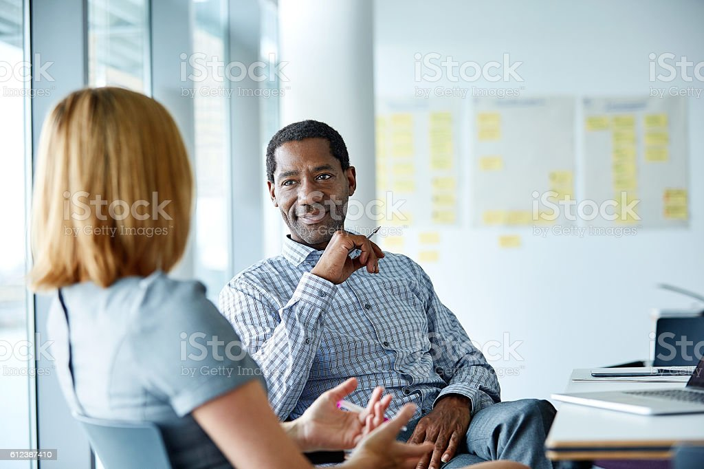 Shot of two colleagues talking together while sitting in a modern...