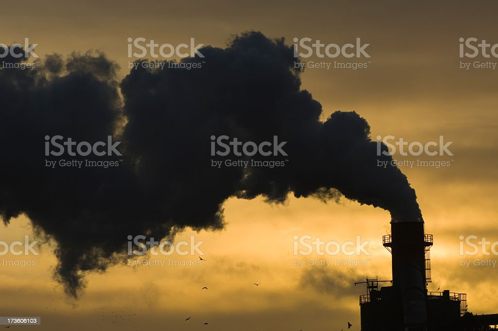 Thick, black pollution smoke against a yellow sky royalty-free stock photo