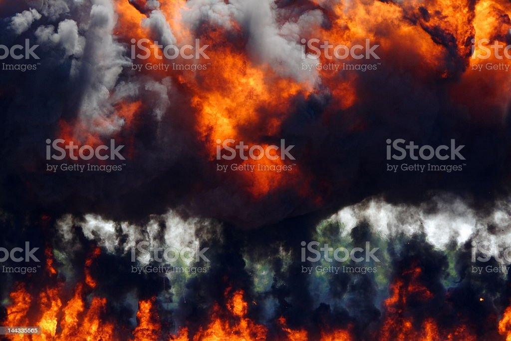 Thick black smoke rising from a flaming explosion stock photo