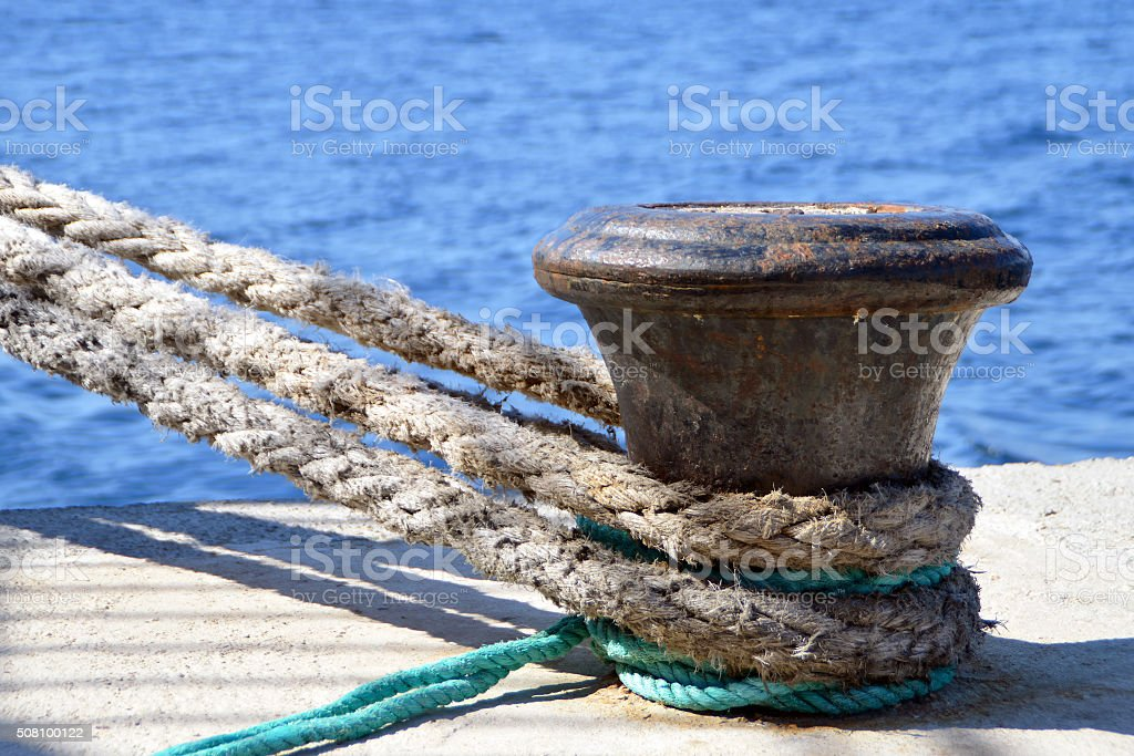 Thick boat ropes tied to an old rusty bollard stock photo