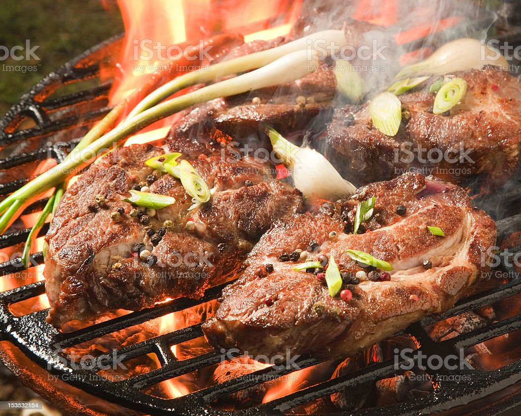 Thick broiled pork steaks on a grill, flames royalty-free stock photo