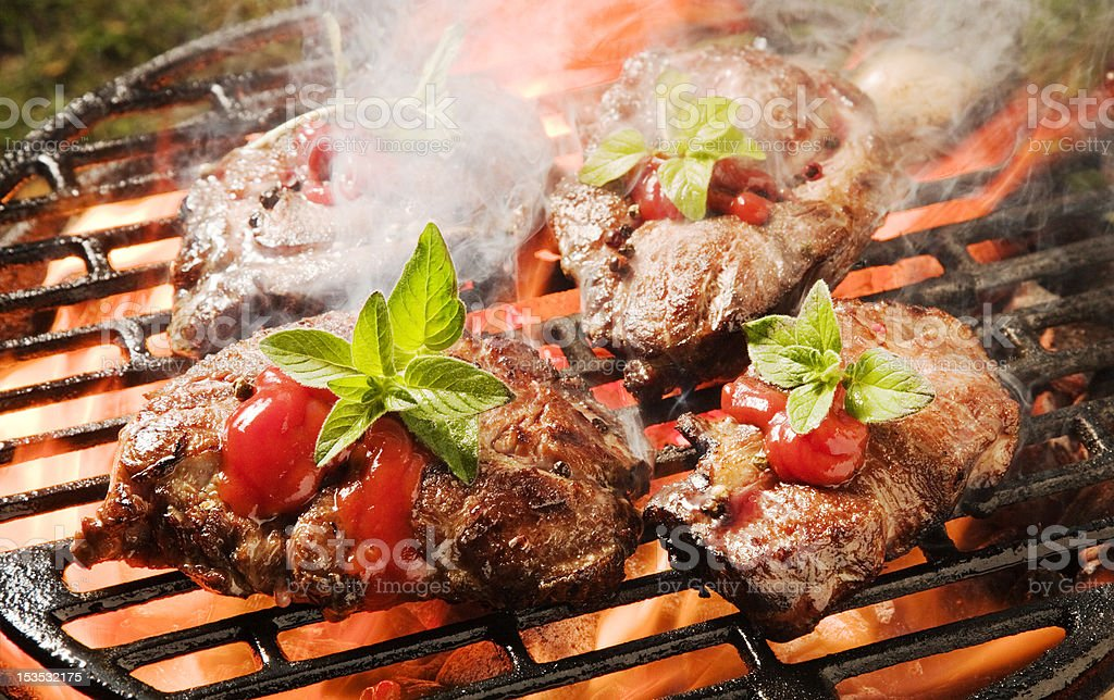 Thick broiled pork steaks on a grill, red marinade, flames royalty-free stock photo