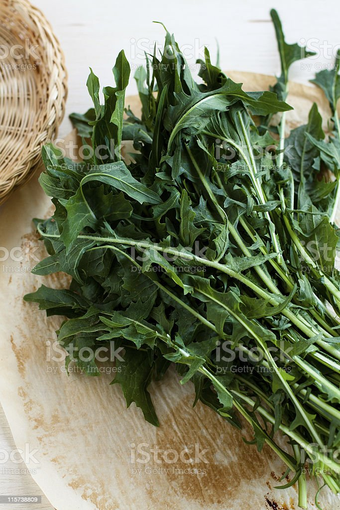 A thick bunch of Dandelion Greens on chopping board stock photo