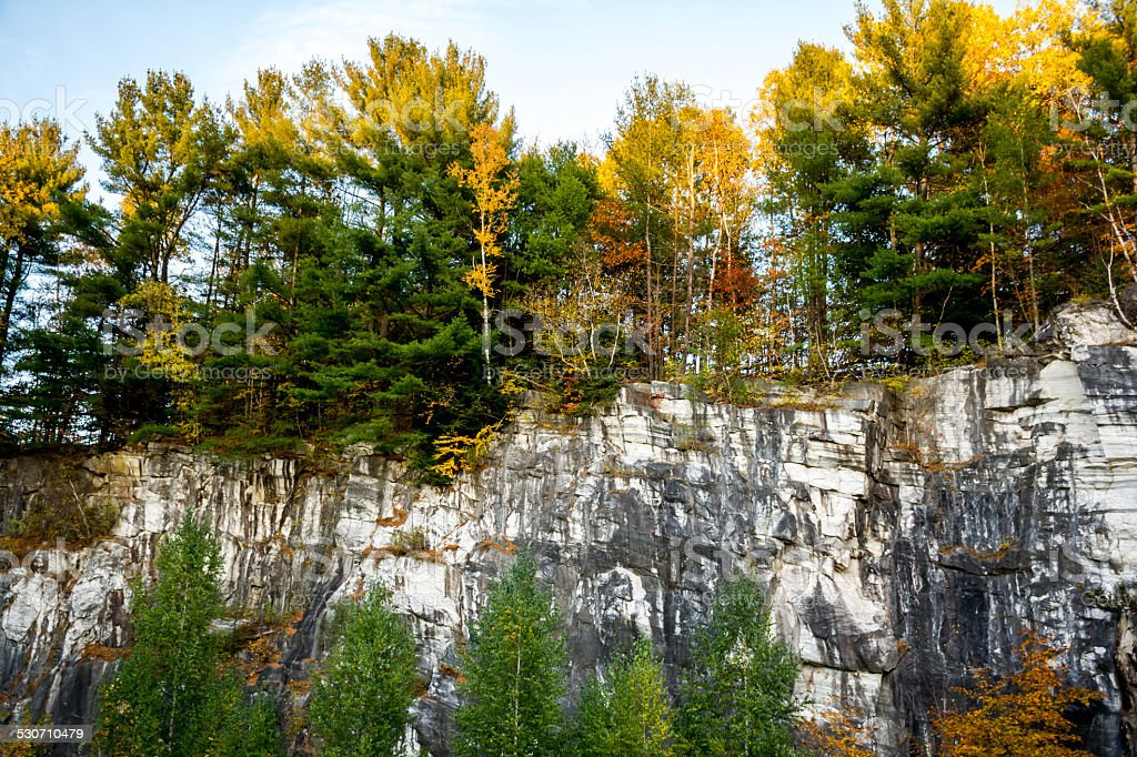 Thick fall foliage and marble rock formation stock photo