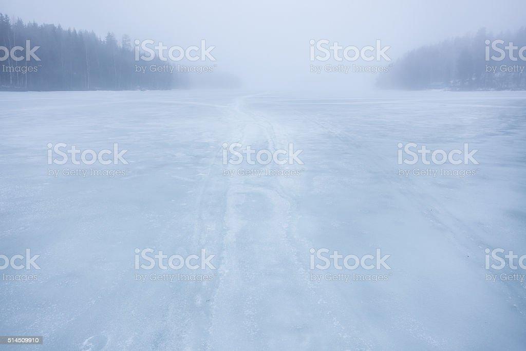 Thick fog at frozen lake landscape stock photo