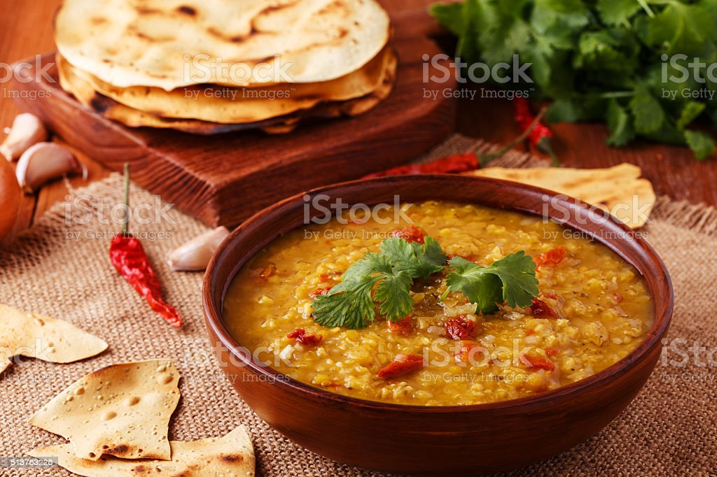 Thick indian red lentil soup with indian flat bread. stock photo