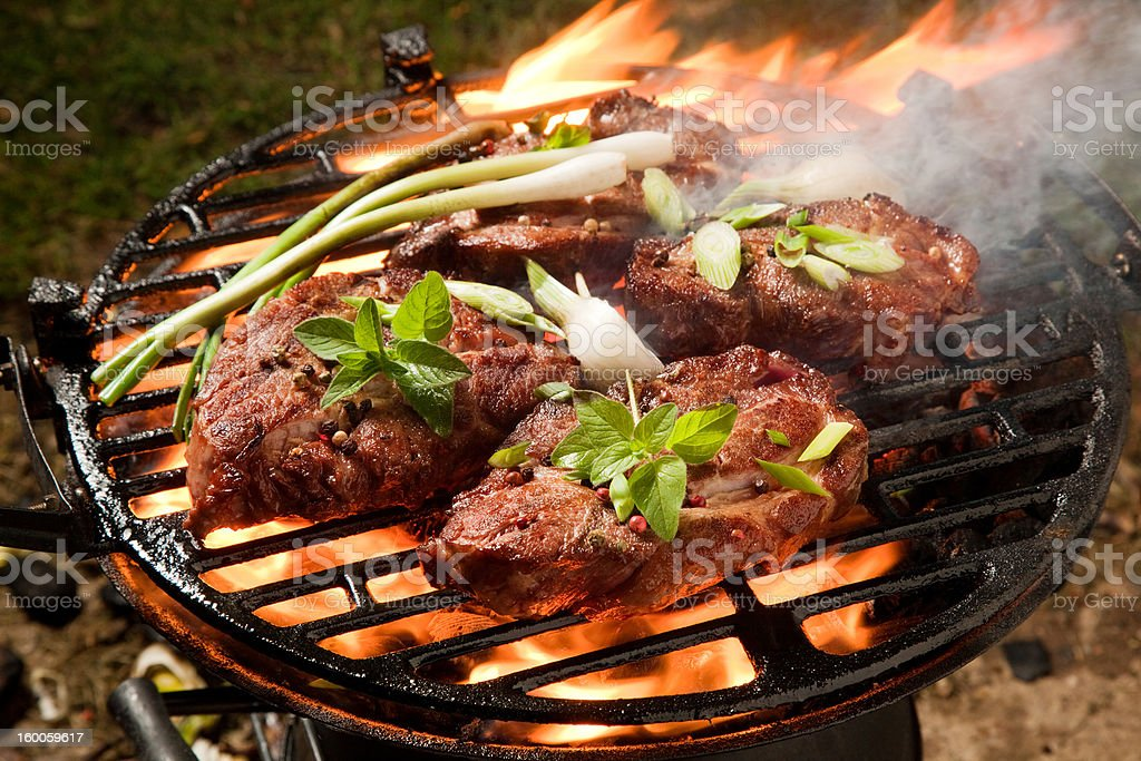 Thick pork steaks on a grill, garnished royalty-free stock photo