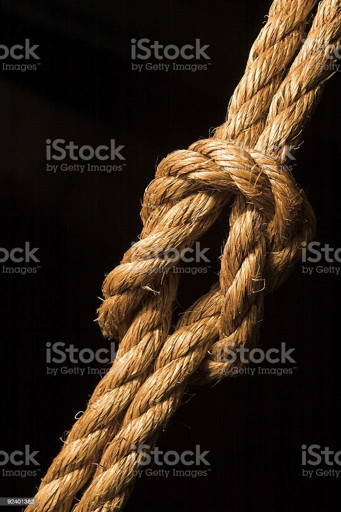 Thick rope tied in a knot on a black background stock photo