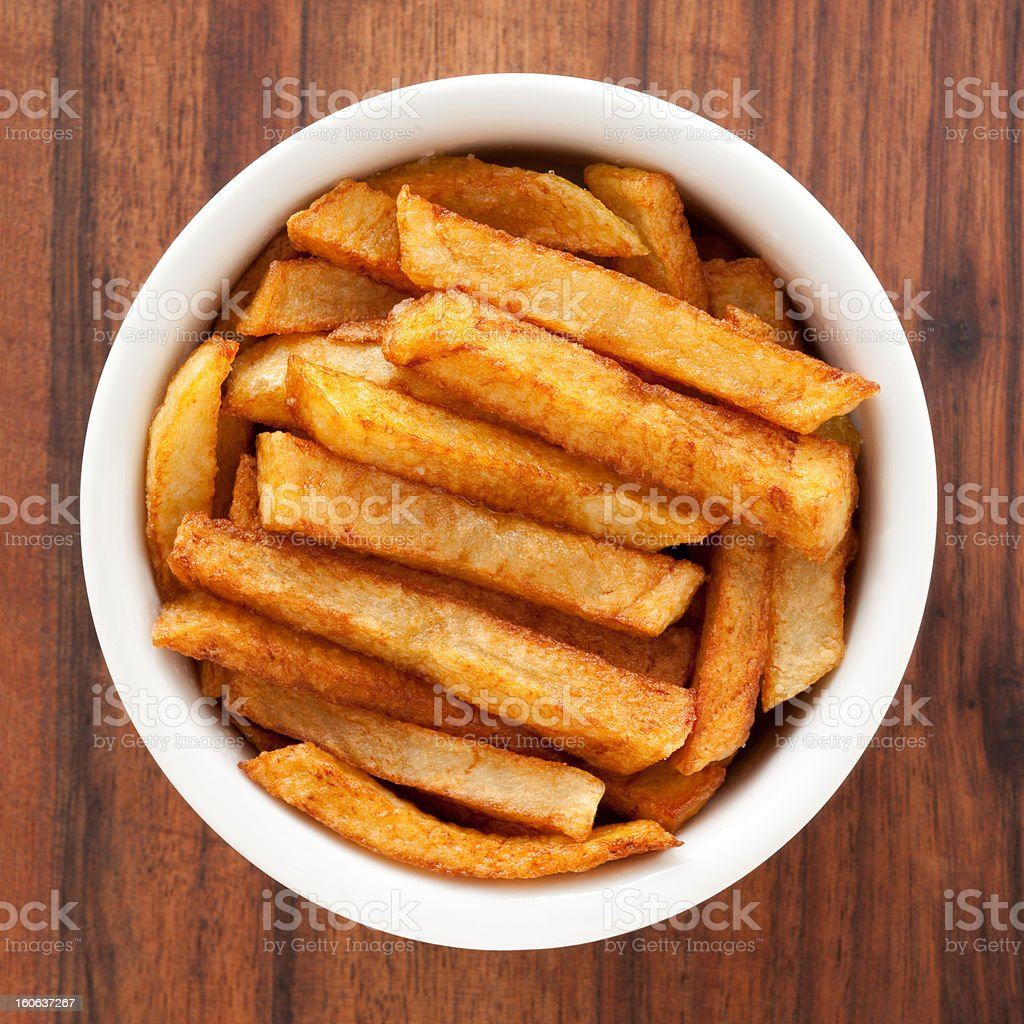 Thick-cut potato fries in a bowl on wood grain stock photo