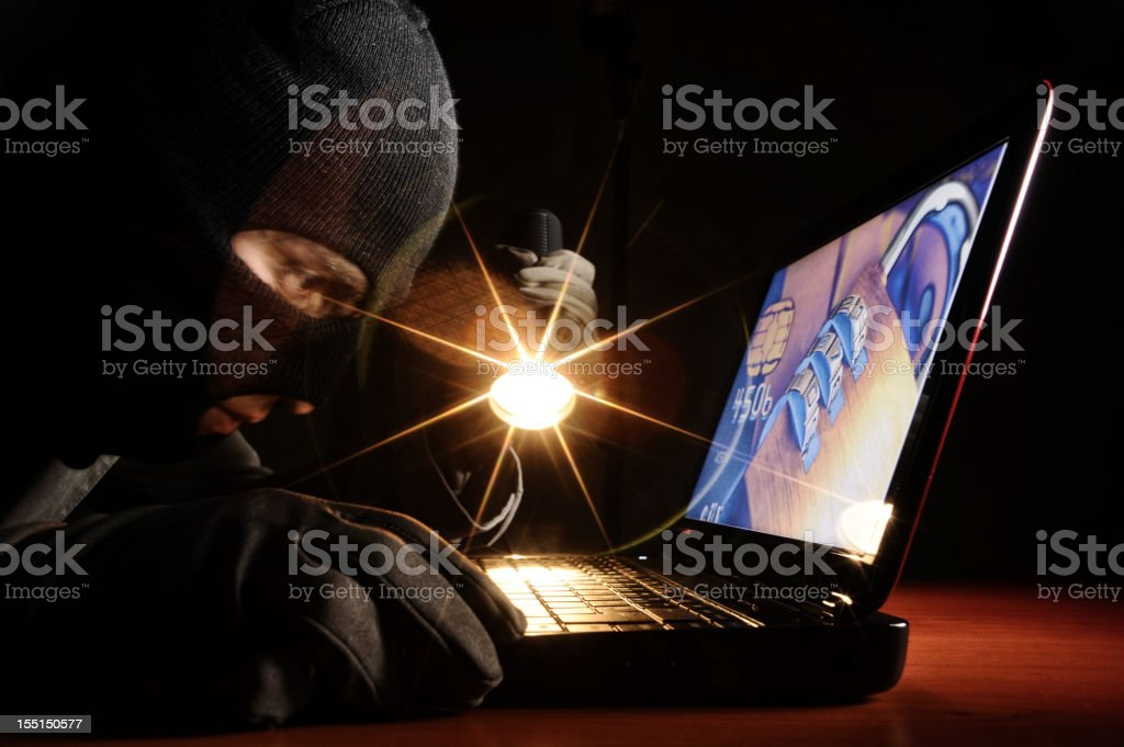 Thief accessing a laptop stock photo