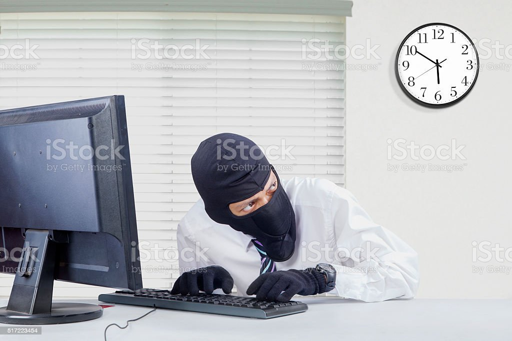 Thief breaking computer in office stock photo