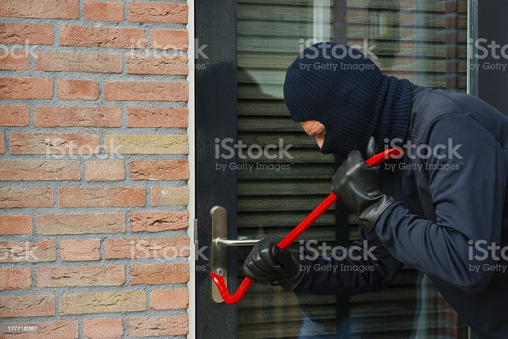 Thief breaking into a home with a crowbar stock photo